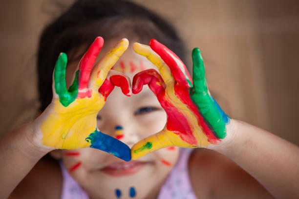Child's hand with painted colorful watercolor make heart shape - foto stock