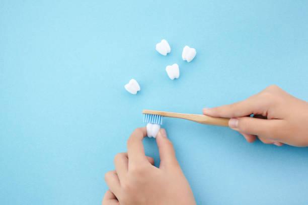 Kinderhand mit Zahnbürste und weißem Platic Zahn auf blauem Hintergrund – Foto