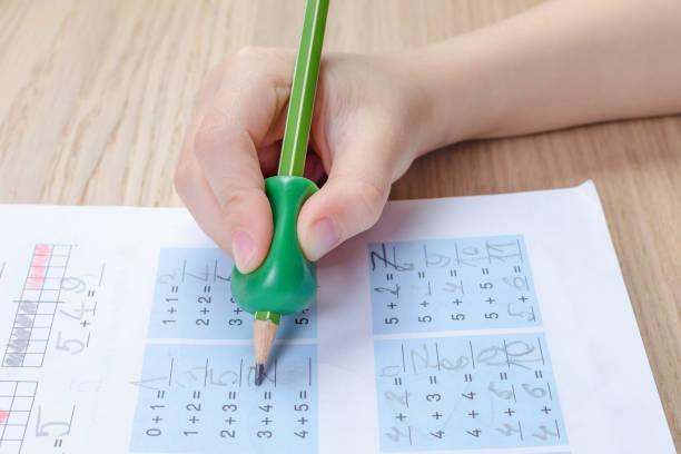 Kinderhand mit Schreibwerkzeug zur Hilfe durch falsches Halten von Bleistift, Heimatwortk, Mathematik – Foto