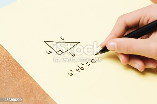 A child's hand is working out Pythagoras' geometry theorem with diagrams on a piece of paper.