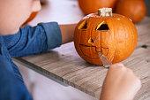 Child's hands carving pumpkin for Halloween