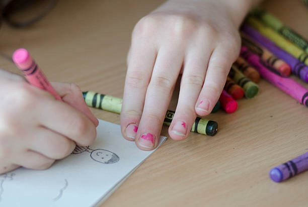 Child's hands colouring a picture with crayons stock photo