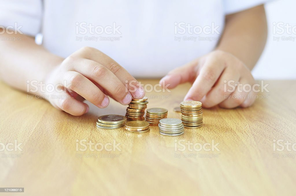 Childs hands counting coins on wooden table top stock photo