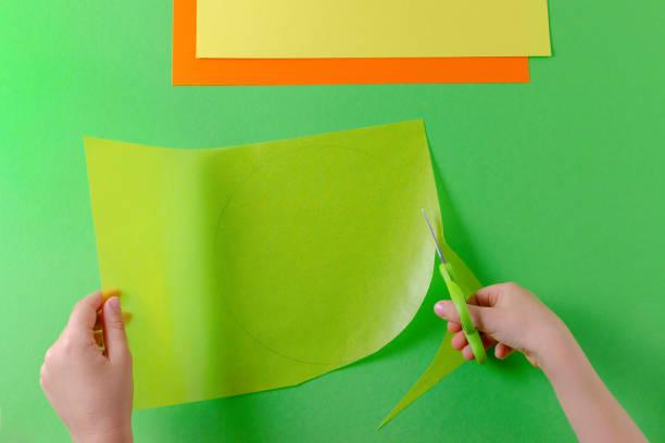 hände des kindes schneiden mit der schere, ansicht von oben auf den grünen kreis auf transparentpapier - diy eule stock-fotos und bilder