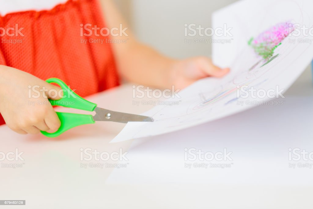 Child's hands cutting paper with scissors royalty-free stock photo