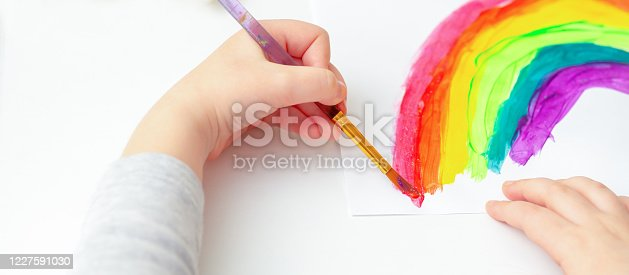 Painted rainbow by the hands of a child with watercolors on a white sheet of paper.
