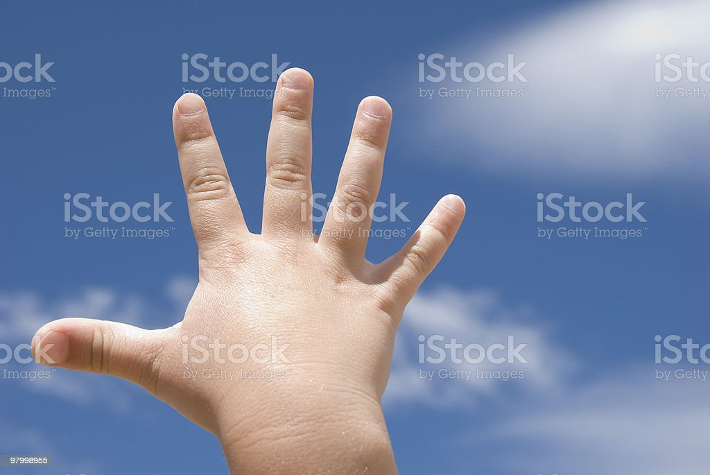 Child's hands extended upward aganst blue sky royalty-free stock photo