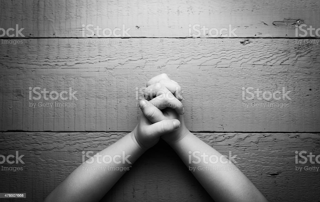 Child's hands folded together in prayer. Black and white photo stock photo