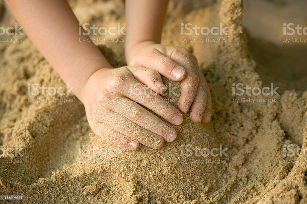 Child's hands forming a cone in sand stock photo