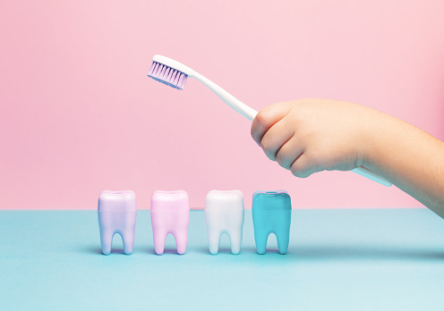 istock Child's hands holding big tooth and toothbrush 1140150290