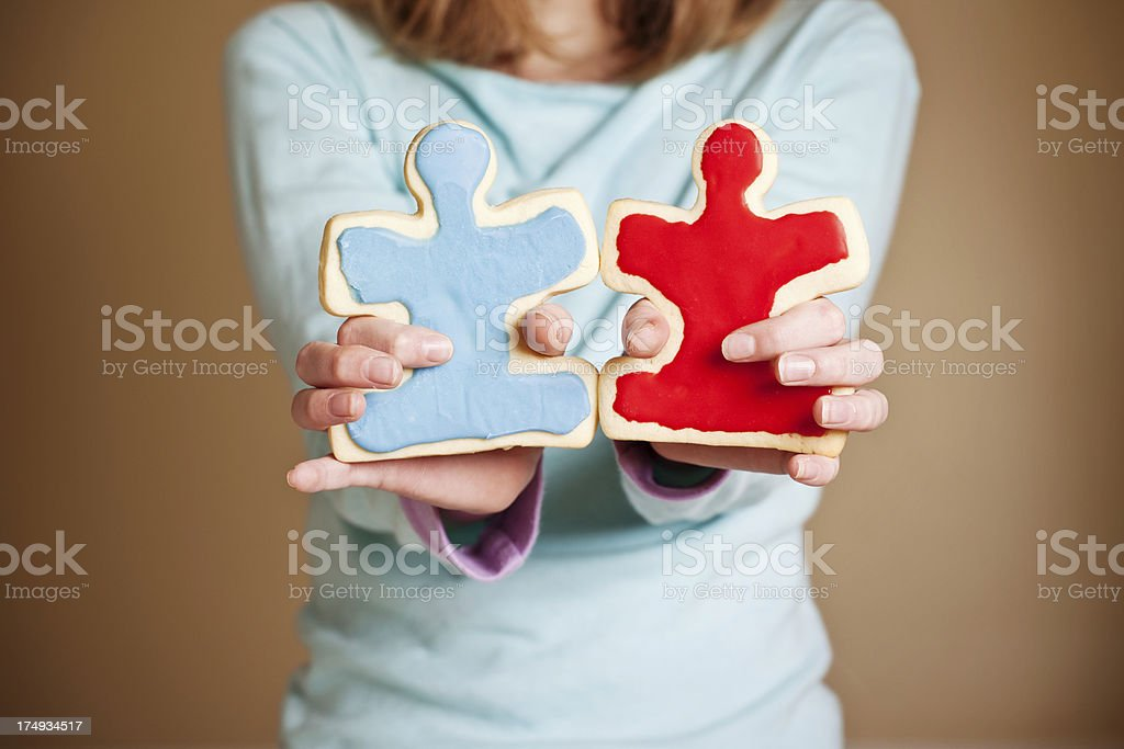 Child's Hands Holding Puzzle Piece Sugar Cookies stock photo