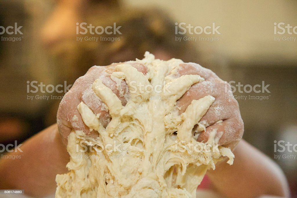 Childs hands squeezing dough through her fingers breadmaking such fun! stock photo
