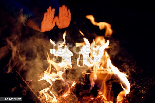 istock Child's hands stretched to burning campfire at night. Warming palms at fire 1134344536