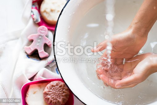 istock Child's hands under white bowl with water upon water stream 851007484