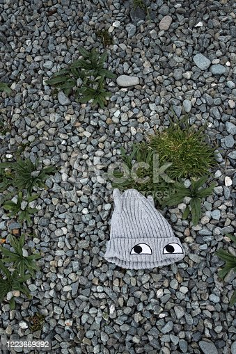 Knitted woollen grey child's beanie hat with eyes, abandoned & lying on ground surrounded by gravel & weeds, viewed from above