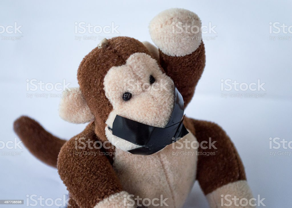 Child's Monkey Toy Raising Hand/Asking a Question Tape Over Mouth stock photo