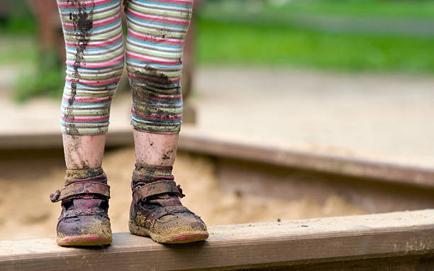 child's muddy feet - dirty shoes stock photos and pictures