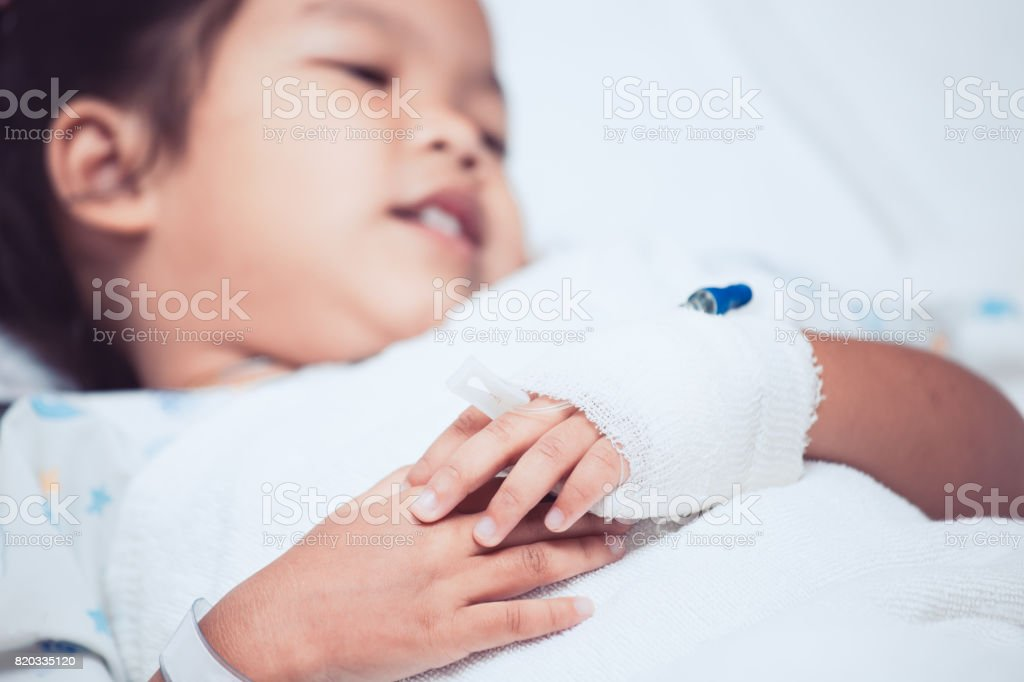 Child's patient hand with saline intravenous (iv) drip in the hospital stock photo
