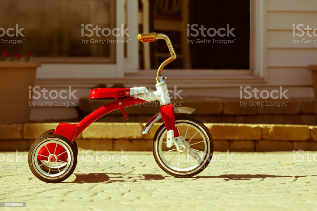 Child's rusted red tricycle standing ready stock photo