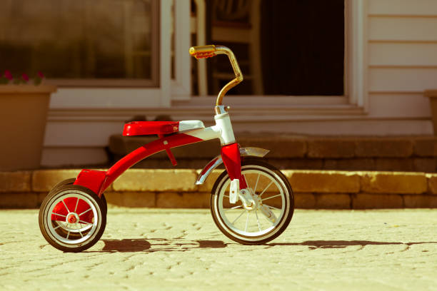 child's rusted red tricycle standing ready - dreirad stock-fotos und bilder