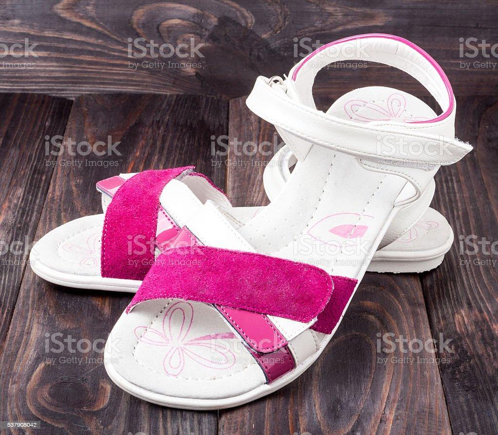 child's sandals on a dark wooden background stock photo