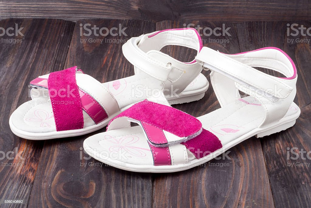 child's sandals on a dark wooden background royalty-free stock photo
