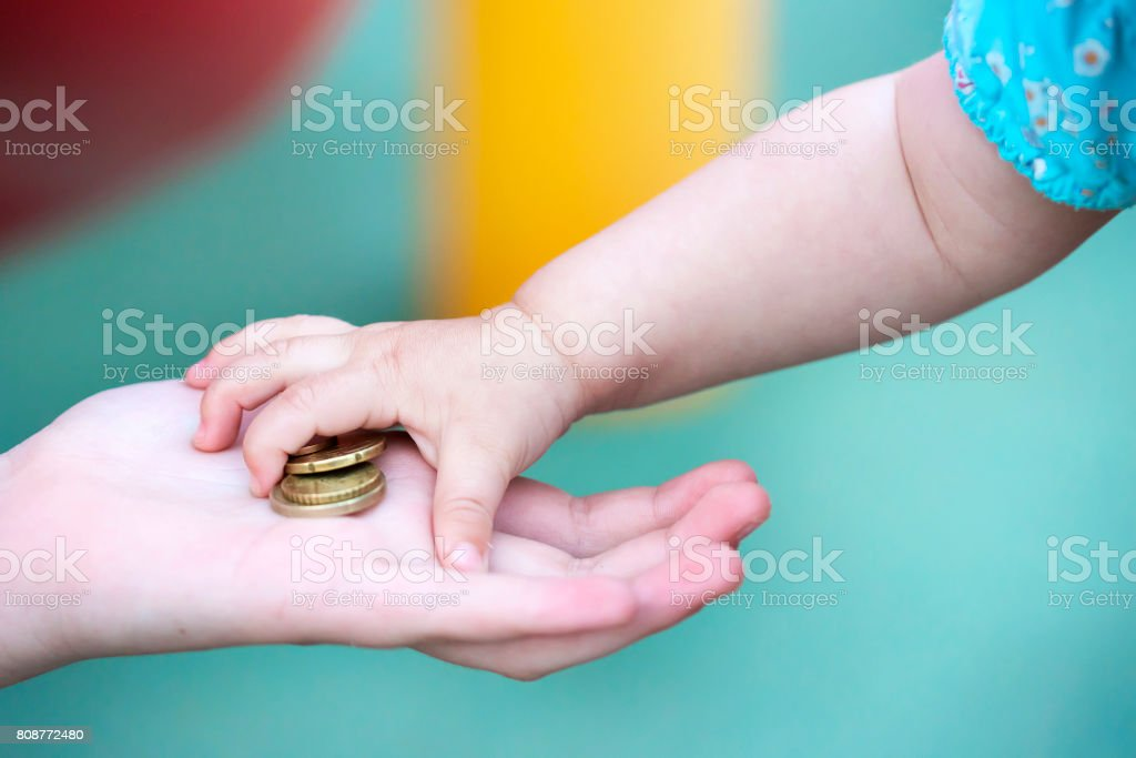 Child's small hand, takes a pile of small money from the palm of your hand. stock photo