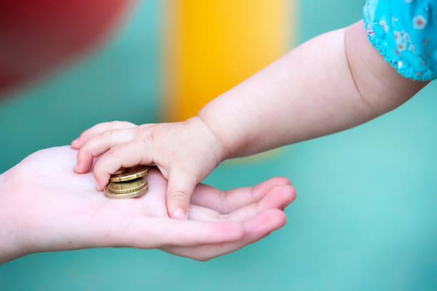 Child's small hand, takes a pile of small money from the palm of your hand. Child's small hand, takes a pile of small money from the palm of your hand allowance stock pictures, royalty-free photos & images