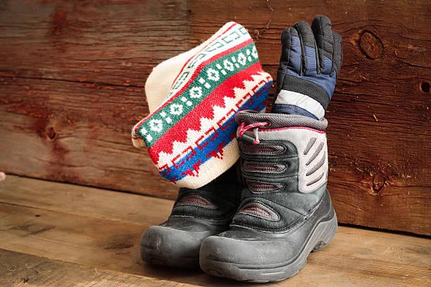 childs schneestiefel mit einer winter mütze und handschuhe - kinder winterstiefel stock-fotos und bilder