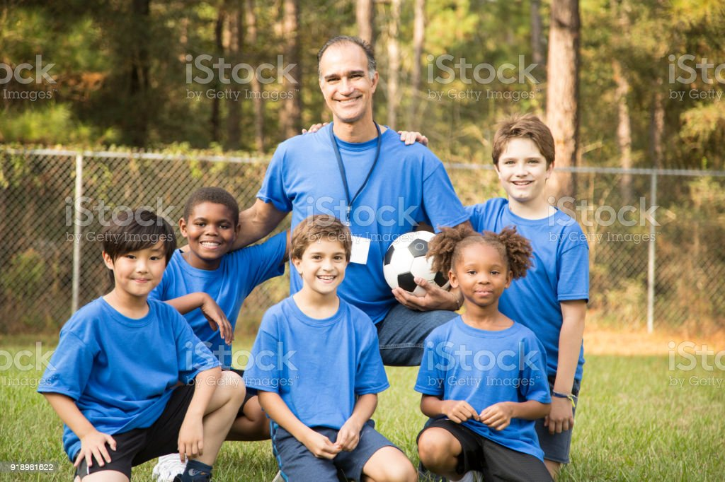Child's soccer team with coach. stock photo