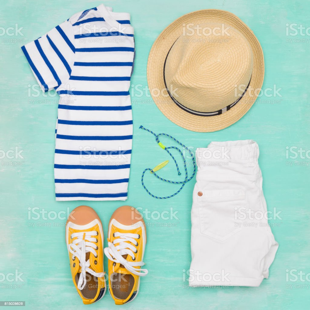 Child's striped t-shirt, denim shorts, accessories, yellow shoes and straw hat on turquoise wooden background. Top view. Flat lay. Kid's summer clothes collage stock photo