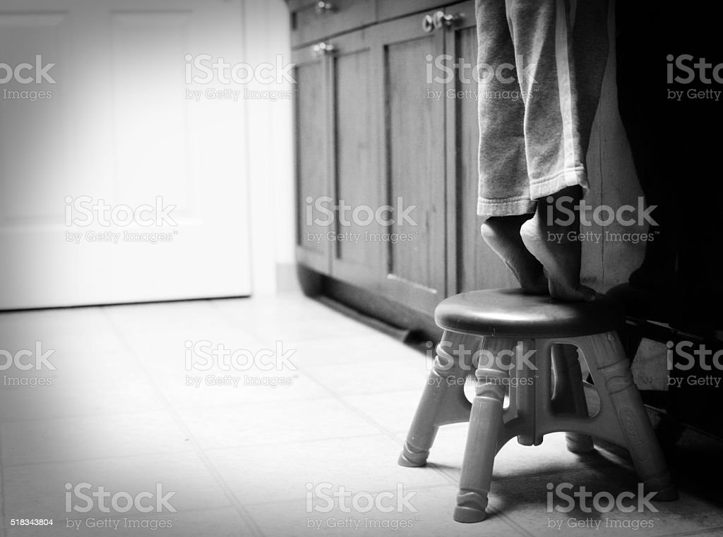 Bambino tippy piedi su sgabello fotografie stock e altre immagini