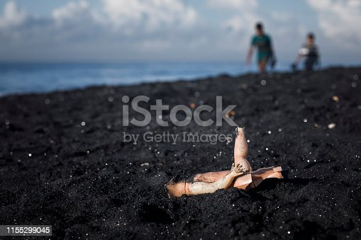 An old Childs doll washed up on a black sand beach.