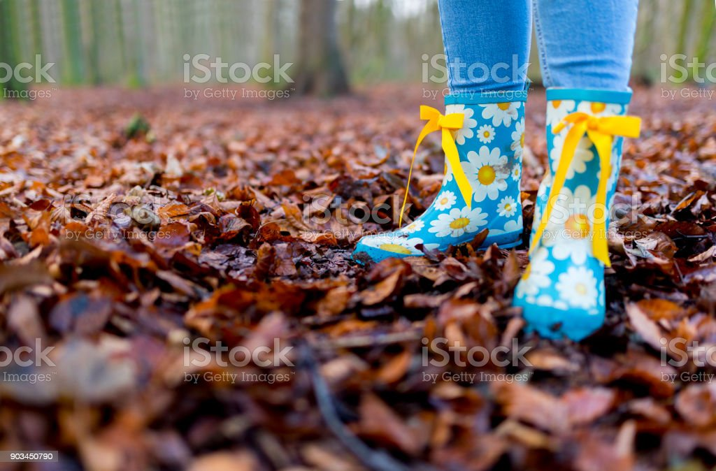 Child\'s wearing sky blue wellies with daisy patterns and yellow bow...