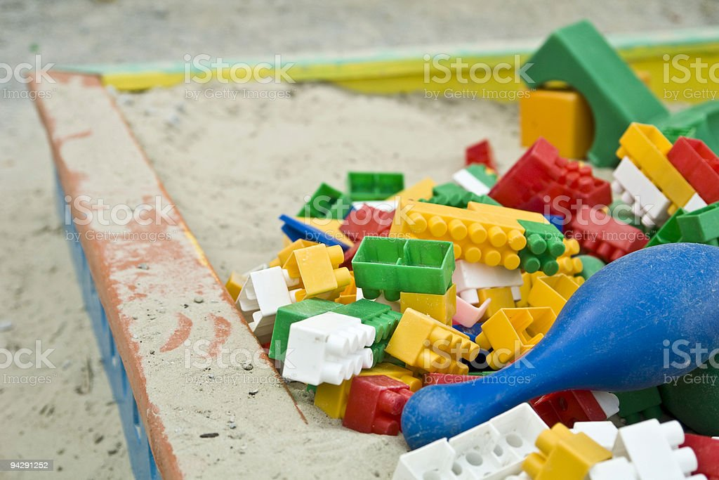 Child's wooden sandbox piled with multicolored Lego pieces stock photo