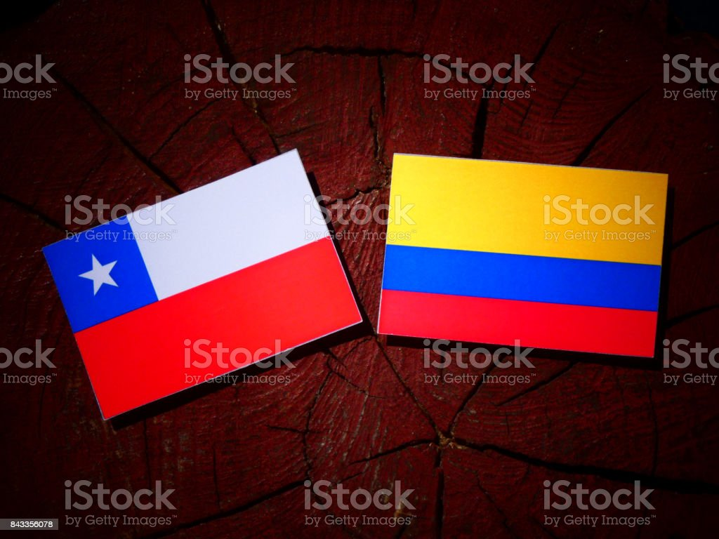 Chilean flag with Colombian flag on a tree stump isolated stock photo