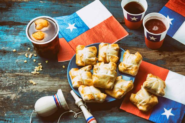 chilenischen unabhängigkeitstag konzept. fiestas patrias. chilenische typische speise und getränke am tag der unabhängigkeit-partei, 18 september. mini-empanadas, mote con huesillo wein mit geröstetem mehl, chicha und typisches spiel emboque - freistaat stock-fotos und bilder