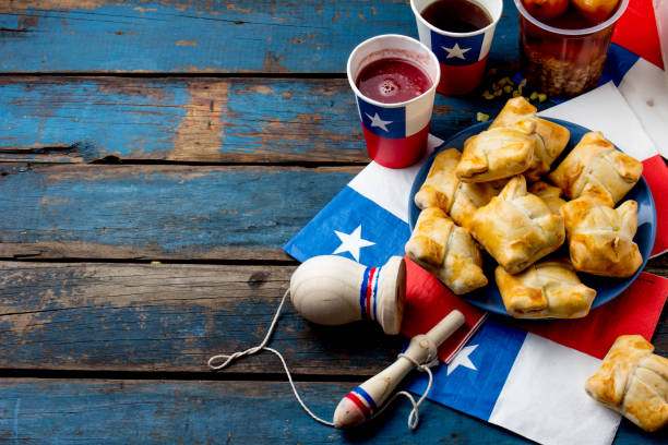 Chilean independence day concept. fiestas patrias. Chilean typical dish and drink on independence day party, 18 september. Mini empanadas, mote con huesillo, wine with toasted flour, chicha and tipical play emboque stock photo