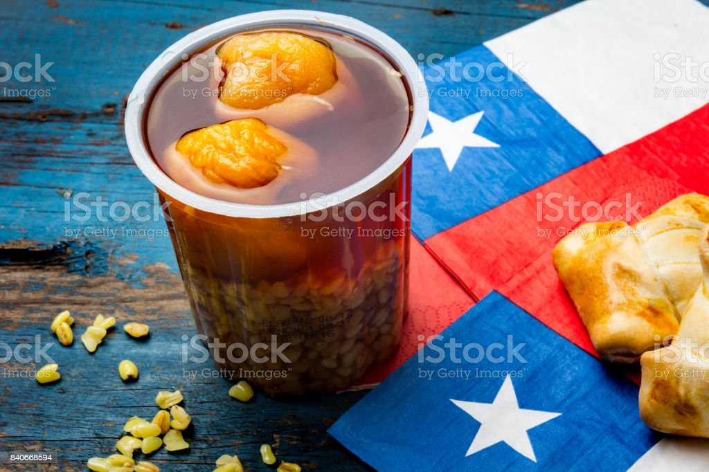 Chilean independence day concept. fiestas patrias. Chilean typical dish and drink on independence day party, 18 september. Mini empanadas, mote con huesillo, wine with toasted flor, chicha and tipical play emboque stock photo