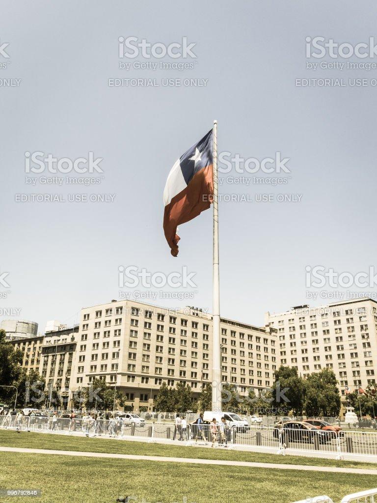 Chilenos andando perto da bandeira gigante na Avenida La Alameda, com a cidadania Square, no centro de Santiago do Chile. Chile. - foto de acervo