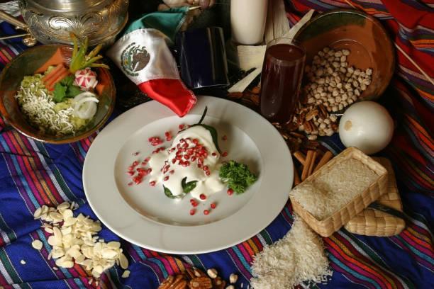 chiles en nogada es un platillo de cocina mexicana. se trata de chiles poblano relleno con picadillo con una salsa de crema base de nuez, llamada nogada y semillas de granada. - bandera de iturbide fotografías e imágenes de stock