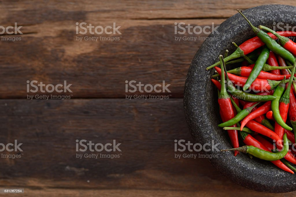 Chili and stone mortar in wooden tone background stock photo