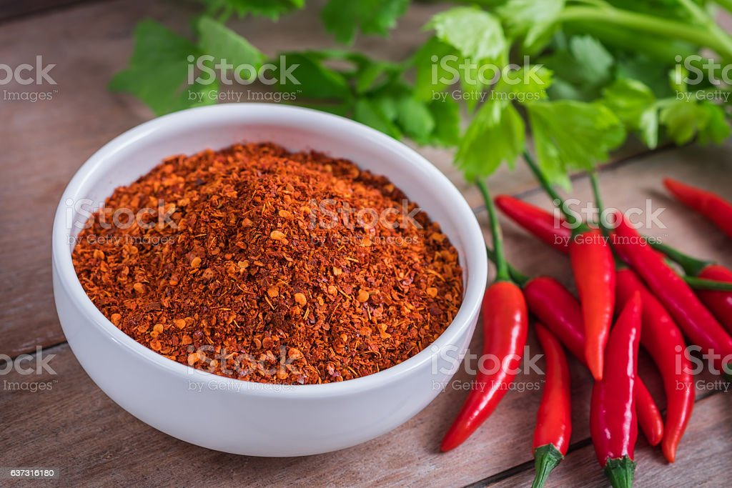 Chili cayenne in bowl and fresh chili on wooden table stock photo