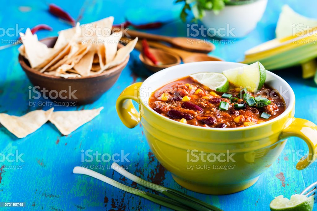 Chili con carne stew served in yellow bowl on rustic blue wooden table stock photo