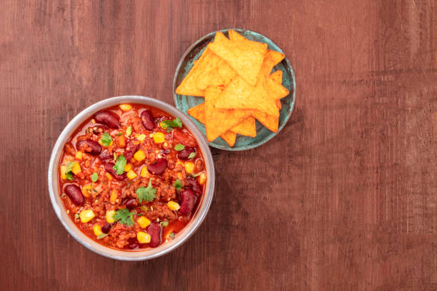 Chili con carne, traditional Mexican dish, overhead photo with nacho chips and copy space An overhead photo of chili con carne, a traditional Mexican dish with red beans, cilantro leaves, ground meat, and chili peppers, with nachos, tortilla chips, and copy space chili con carne stock pictures, royalty-free photos & images