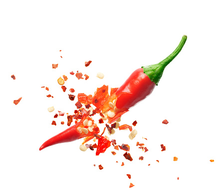 Chili flakes bursting out from red chili pepper over white background