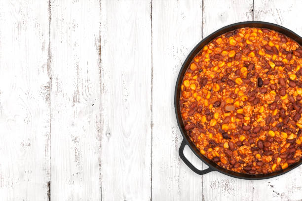 Chili On Light Background Hot chili con carne in a cast iron pan on light wooden background, top view chili con carne stock pictures, royalty-free photos & images