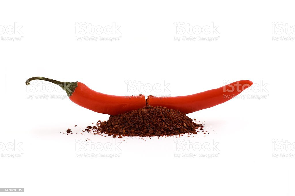Chili pepper cut in half with spice pouring out royalty-free stock photo
