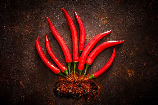 Close up view of ripe red chili peppers making a flame shape on rustic brown background. Low key DSRL studio photo taken with Canon EOS 5D Mk II and Canon EF 100mm f/2.8L Macro IS USM.