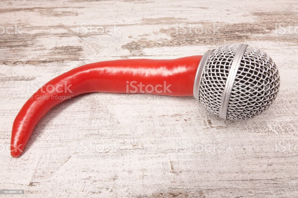 Chili Pepper With Microphone On Wooden Tablecloth Royalty Free Stock Photo
